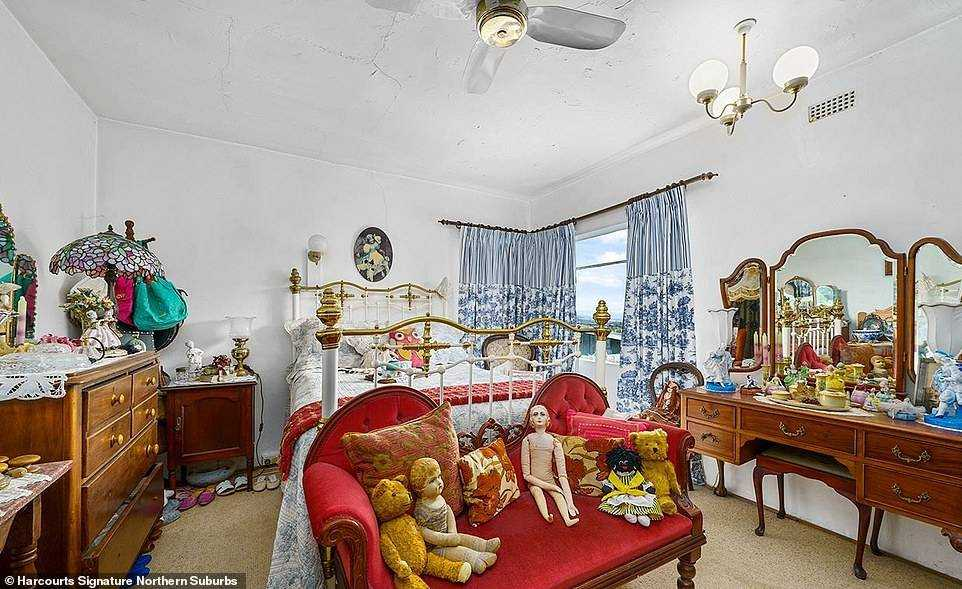 In one bedroom, a red living room is decorated with a naked doll and a controversial Golliwog among many other teddy bears and bric-a-brac