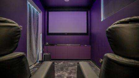 A purple movie theater in the architect's house at Hillside Road, Portishead for sale.  Large screen, gray carpet and curtain separating it from the living rooms and two leather armchairs in the foreground.