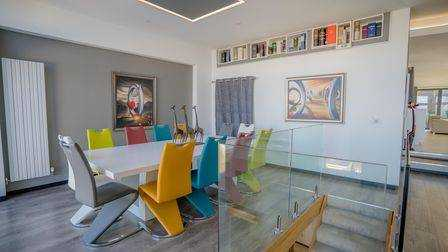 Modern dining room in Home for Sale in Hillside Road Portishead with colorful chairs around a white plastic dining table.